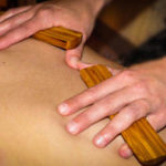 Hands massaging a back with bamboo pieces.